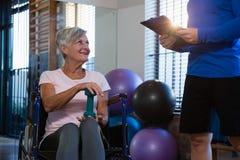 Donna senior che interagisce con il fisioterapista Fotografia Stock