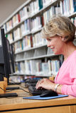 Donna senior che lavora al computer in biblioteca Immagine Stock Libera da Diritti