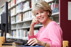 Donna senior che lavora al computer in biblioteca Fotografie Stock