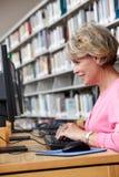 Donna senior che lavora al computer in biblioteca Fotografia Stock