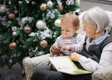 Donna senior che legge un libro al suo nipote del bambino accanto ad un albero di Natale Immagini Stock