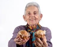 Donna senior che mangia bigné su fondo bianco fotografia stock libera da diritti