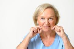 Donna senior che mostra il suo fronte, effetto di invecchiamento Fotografia Stock