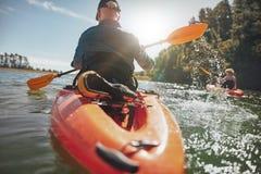Donna senior che ottiene le lezioni di kayak da un uomo immagini stock
