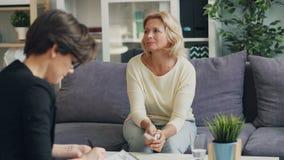 Donna senior che parla con terapista che discute i problemi nell'ufficio moderno stock footage