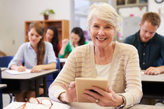 Donna senior che per mezzo del computer della compressa alla classe di corsi per adulti fotografia stock libera da diritti