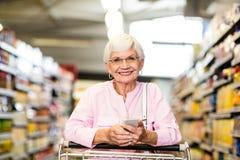 Donna senior che per mezzo del telefono mentre spingendo carretto Immagine Stock Libera da Diritti