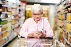 Donna senior che per mezzo del telefono mentre spingendo carretto Immagini Stock