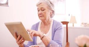 Donna senior che per mezzo della compressa digitale mentre mangiando prima colazione video d archivio
