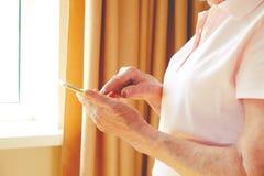Donna senior che per mezzo dello Smart Phone a casa fotografia stock libera da diritti