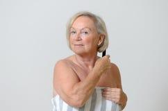Donna senior che pettina i suoi capelli Fotografie Stock Libere da Diritti