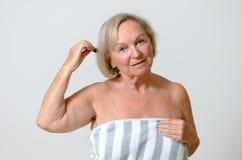 Donna senior che pettina i suoi capelli Immagini Stock