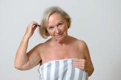Donna senior che pettina i suoi capelli Immagine Stock