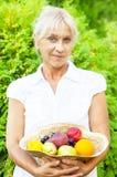 Donna senior che porta un cappello in pieno della frutta fresca Immagine Stock