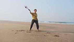 Donna senior che pratica la palla del pallone di 'chi' del tai sulla spiaggia video d archivio