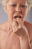 Donna senior che prende una pillola Immagine Stock