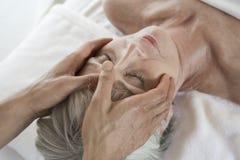 Donna senior che riceve massaggio capo alla stazione termale Immagini Stock Libere da Diritti