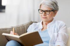 Donna senior che scrive al taccuino o al diario a casa fotografia stock libera da diritti