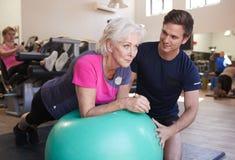 Donna senior che si esercita sulla palla svizzera che è incoraggiata dall'istruttore personale In Gym fotografie stock libere da diritti