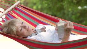 Donna senior che si rilassa in amaca con il libro stock footage