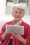 Donna senior che si rilassa con il suo computer portatile fotografie stock libere da diritti