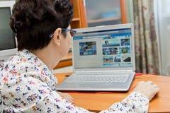 Donna senior che si siede al taccuino e che guarda le immagini sui siti di viaggio Fotografie Stock
