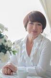 Donna senior che si siede al tavola-verticale Fotografie Stock Libere da Diritti