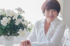 Donna senior che si siede alla tavola Fotografia Stock