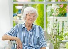 Donna senior che si siede a casa immagine stock