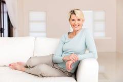 Donna senior che si siede a casa immagini stock