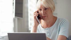 Donna senior che si siede a casa con il computer portatile e lo smartphone Discussione del progetto sullo schermo dal cellulare video d archivio