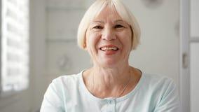 Donna senior che si siede a casa conversazione via il messaggero app Skype Mano d'ondeggiamento sorridente nel saluto archivi video