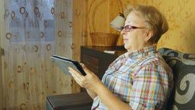 Donna senior che si siede in sofà con la compressa elettronica Immagini Stock Libere da Diritti