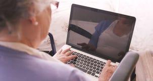 Donna senior che si siede sulla sedia a rotelle che per mezzo del computer portatile stock footage