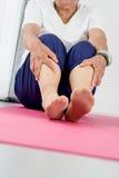 Donna senior che si siede sulla stuoia di yoga Immagini Stock Libere da Diritti