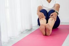 Donna senior che si siede sulla stuoia di yoga Immagine Stock