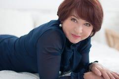 Donna senior che si trova sul sofà Fotografie Stock