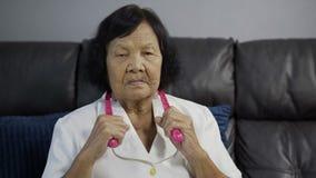 Donna senior che soffre dal dolore al collo e che massaggia dagli strumenti dell'assistente di massaggio video d archivio