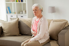 Donna senior che soffre dal dolore di stomaco a casa Fotografie Stock