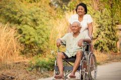 Donna senior che spinge il suo marito disabile sulla sedia a rotelle Fotografia Stock Libera da Diritti