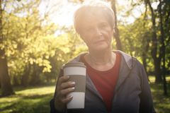 Donna senior che sta nel parco che esamina macchina fotografica e tenuta immagine stock