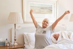 Donna senior che sveglia con un allungamento di mattina Fotografia Stock Libera da Diritti