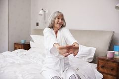 Donna senior che sveglia e che allunga nella camera da letto fotografia stock libera da diritti