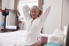 Donna senior che sveglia e che allunga nella camera da letto immagine stock
