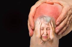 Donna senior che tiene il ginocchio con dolore Immagini Stock