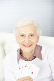 Donna senior che tiene quattro assi Immagini Stock