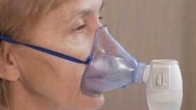 Donna senior che tiene una maschera da un inalatore a casa Tratta l'infiammazione delle vie aeree tramite nebulizzatore Impedire  archivi video
