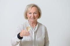 Donna senior che tosta con il champagne Immagine Stock