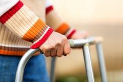 Donna senior che usando un camminatore Immagini Stock