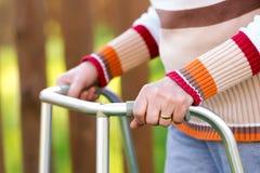 Donna senior che usando un camminatore Fotografia Stock
